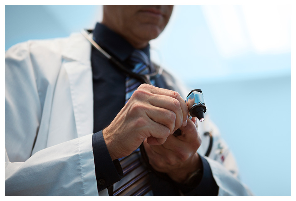 Eye doctor adjusting otoscope for an eye exam testing for glaucoma