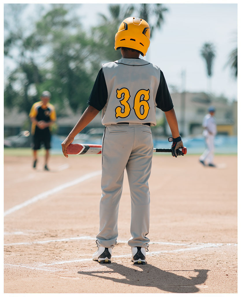 Boy in baseball uniform with bat on baseball field