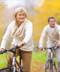 Mature woman and man bicycling on UCHealth executive health page