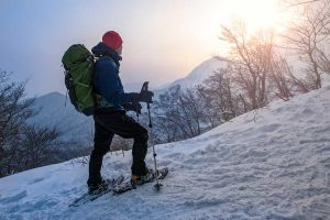 Man with backpack snowshoeing up slope
