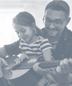 Father and young daughter playing guitar