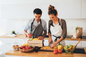 Man and woman cutting vegetables in the kitchen
