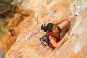 Woman climbing rock face