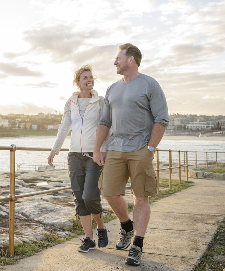 Woman and man walking on path by a bay