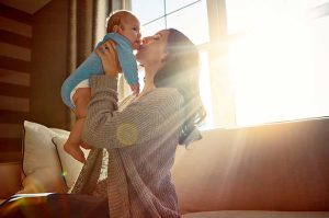 Mother holding baby near sunlit window