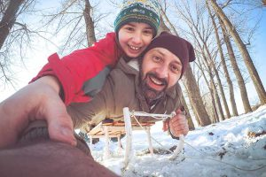 Two people pose in a sledding selfie