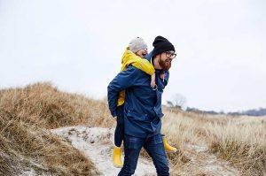 Daughter riding piggyback on dad