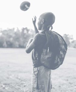 Child with backpack outdoors catching a football