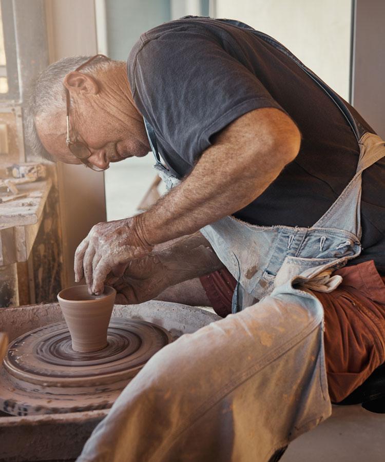 Man making small flowerpot on pottery wheel