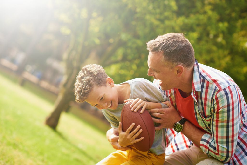 Father and young son with football in park