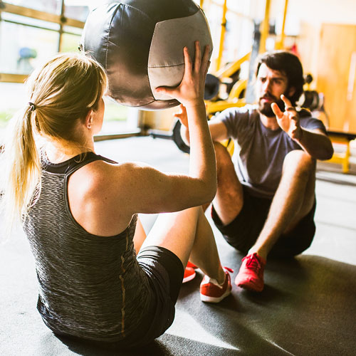 Man and woman exercising in a gym
