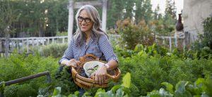 Smiling woman harvesting vegetables in garden