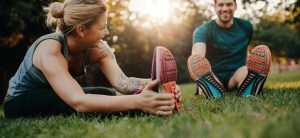 Woman and man stretching on park grass