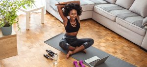 Woman sitting on yoga mat with laptop nearby