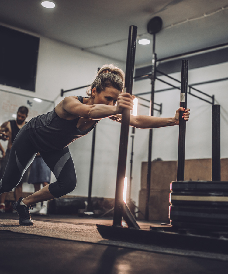 Woman doing standing stretches in gym
