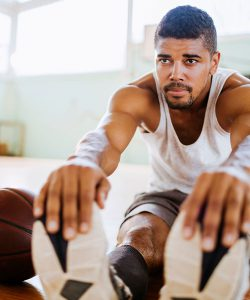 man stretching on basketball court