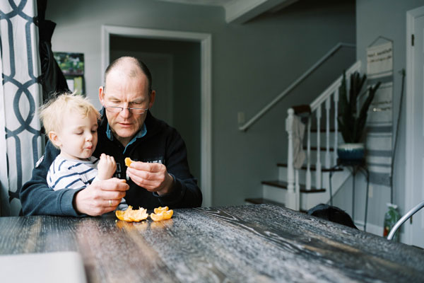 grandfather with grandson on lap eating an orange