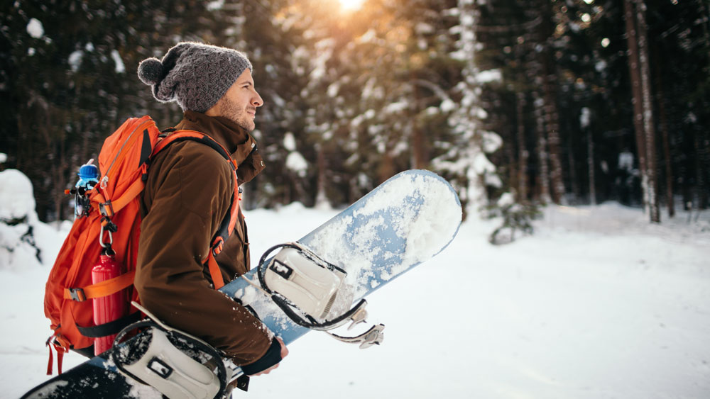 snowboarder walking with board