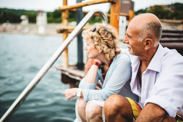 Man and lady sitting on a dock