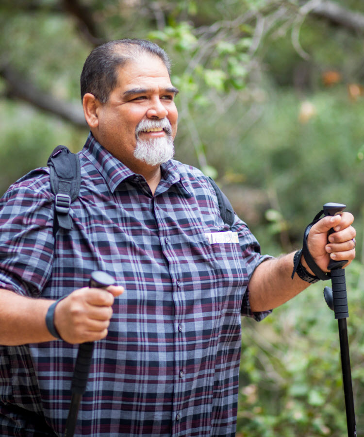 Bearded man in blue shirt with hiking poles