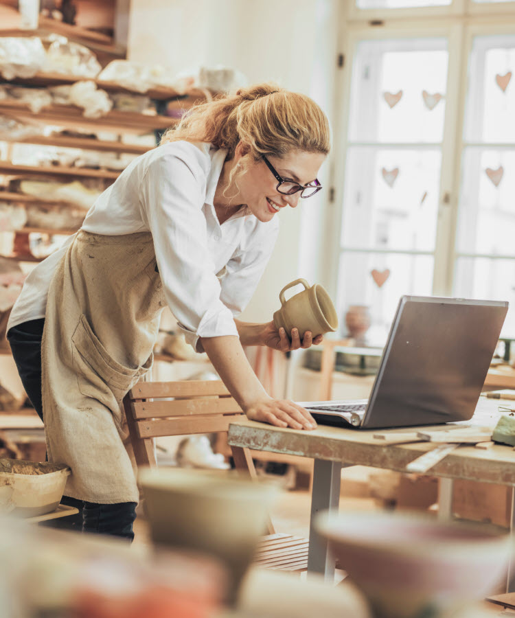 Woman looking at laptop in pottery studio