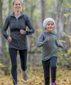 Mother and daughter running through autumn woods