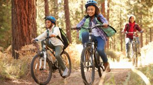 Mother and kids mountain biking on sunlit trail