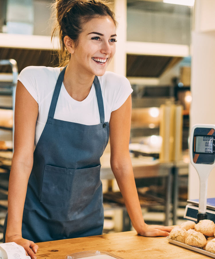 Smiling woman behind bakery counter