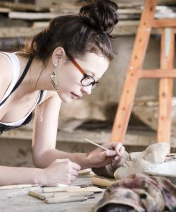 Young woman artist painting a clay face