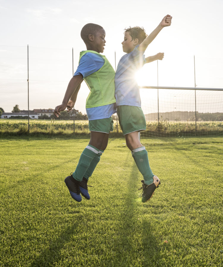 Two boys jumping in celebration on the soccer field