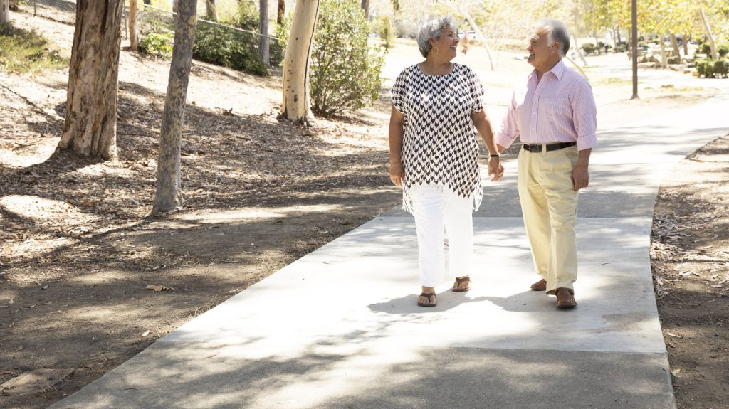 Older couple holding hands on path