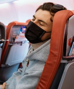 Young man with mask sleeping in airplane seat
