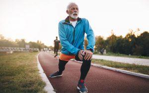 Senior man stretching on running track hero