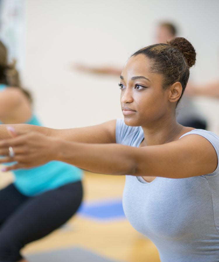 Women at workout class doing squats