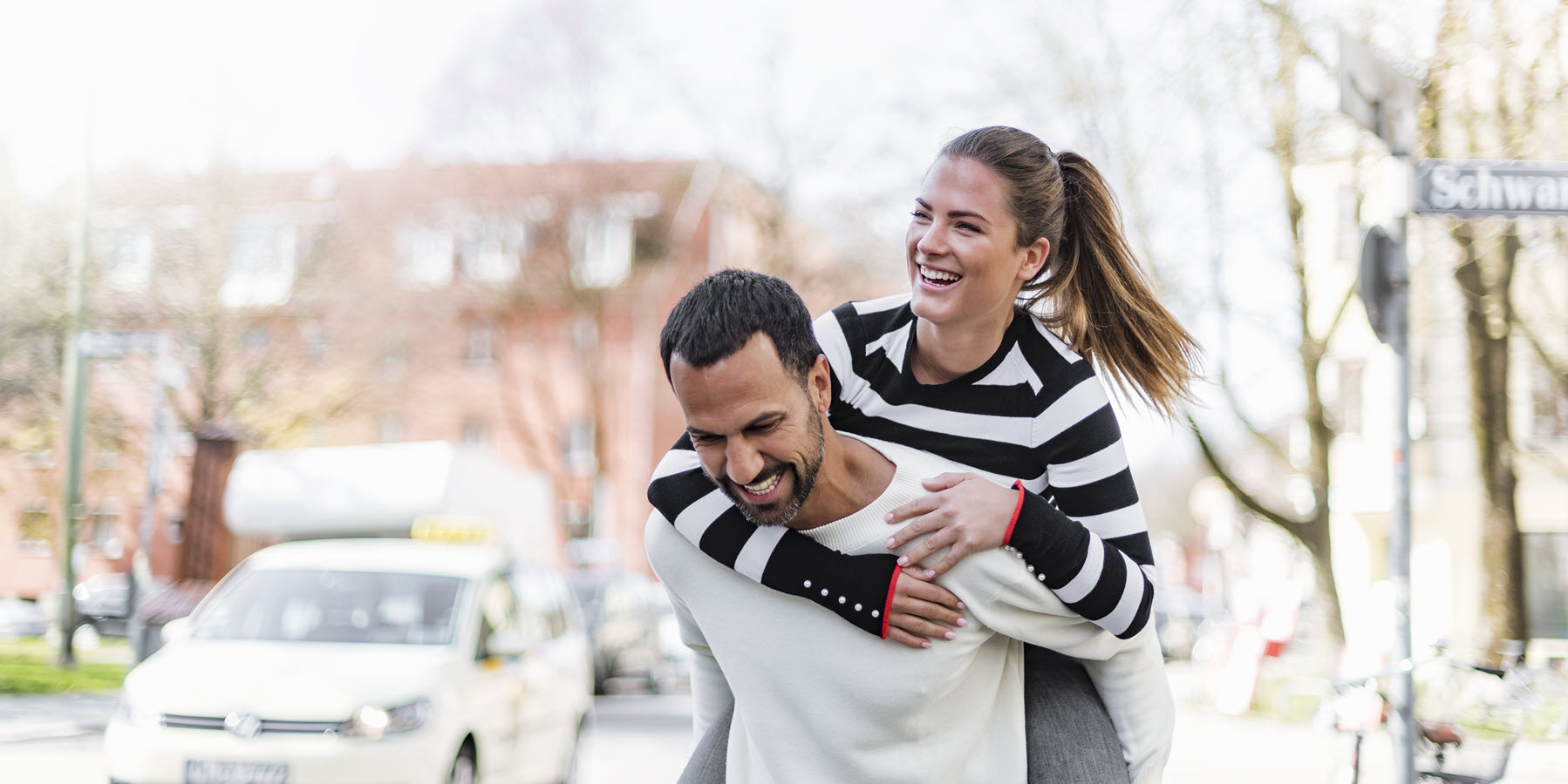 Young woman riding piggyback on man in urban setting