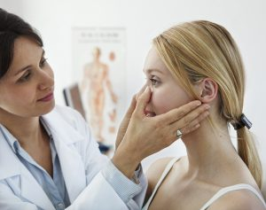 Doctor examining young woman's face