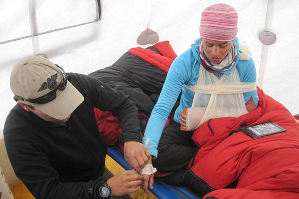 Kim Hess inside a tent with her injured hand in a splint - UCHealth