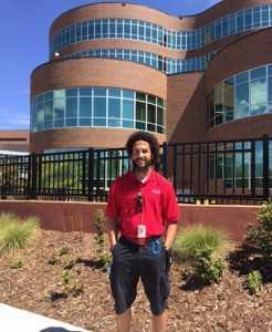 Michael Maxey, a valet and a new father, poses in front of Memorial Hospital.