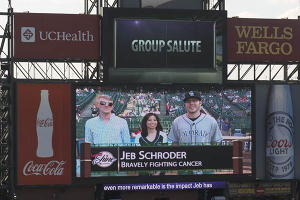 """A sign at Coors Field shows Jeb Schroder with his doctors during a Rockies game. The scoreboard says, """"Jeb Schroder: Bravely Fighting Cancer."""""""