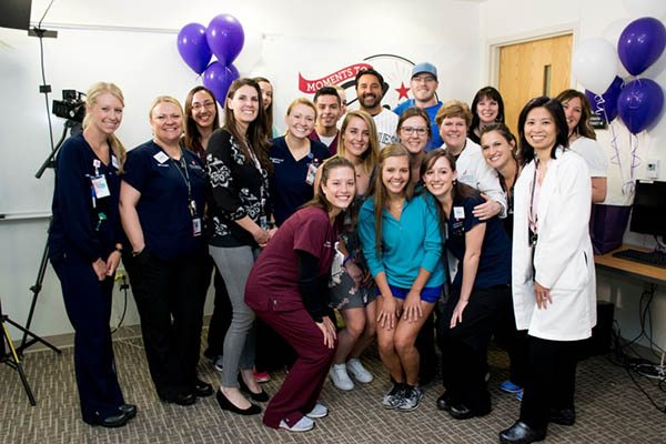 Schroder, a young man who coped with testicular cancer, poses with former Colorado Rockies player, Vinny Castillo, at the UCHealth University of Colorado Cancer Center. This is a big group photo with balloons.