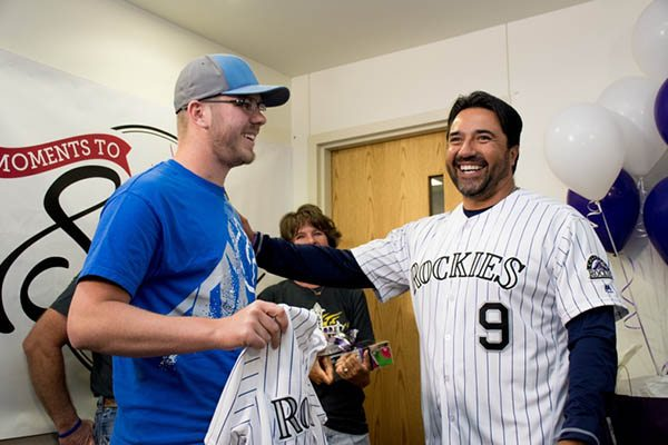 Jeb Schroder, a patient who coped with testicular cancer gets to meet former Colorado Rockies player, Vinny Castilla. Castilla is wearing his Rockies jersey and is handing one to Schroder.