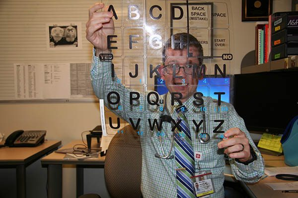 William Niehaus, MD holding a letter board that can be used to help stroke patients communicate | UCHealth