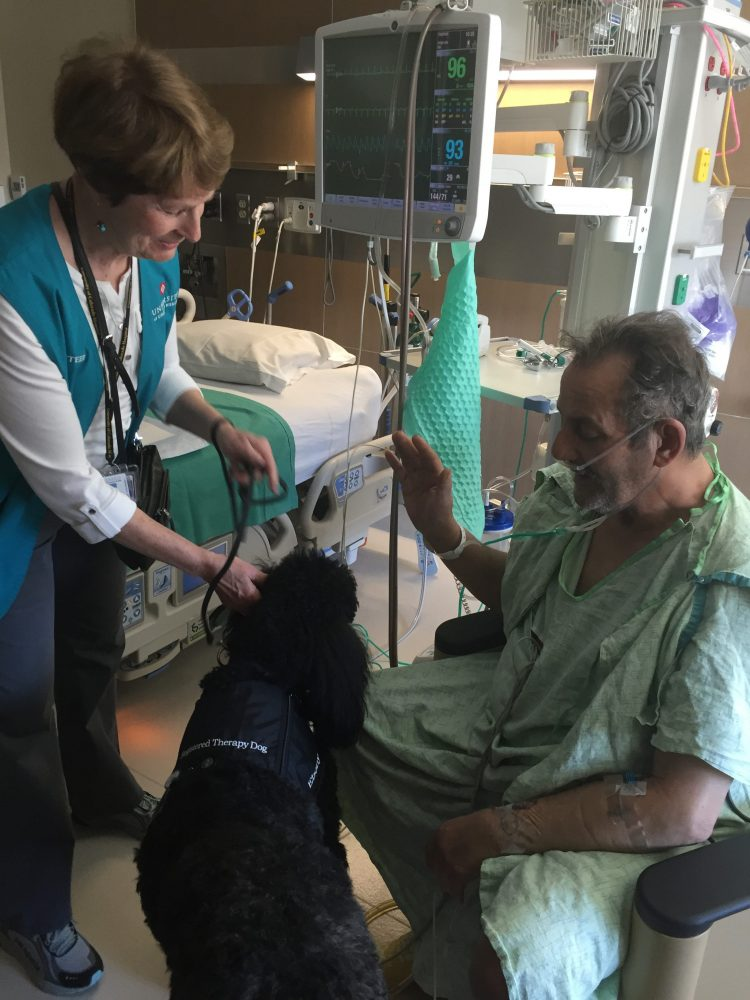 UCH volunteer Alice Jensen and her dog Ebony cheer up patient Anthony Troutner.
