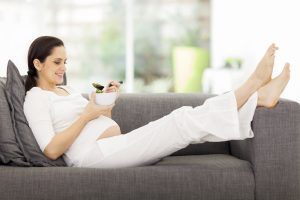 pregnant woman eating veggies on a couch