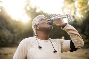 older man drinks water after a workout