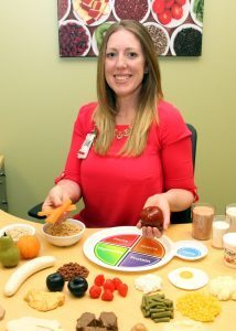 Certified oncology dietitian Liz Nyce uses rubber food to demonstrate portion sizes to her patients. Nyce, who is based out of UCHealth Cancer Center in Fort Collins, also visits patients in Loveland and Greeley and is an integral part of the cancer-fighting team.