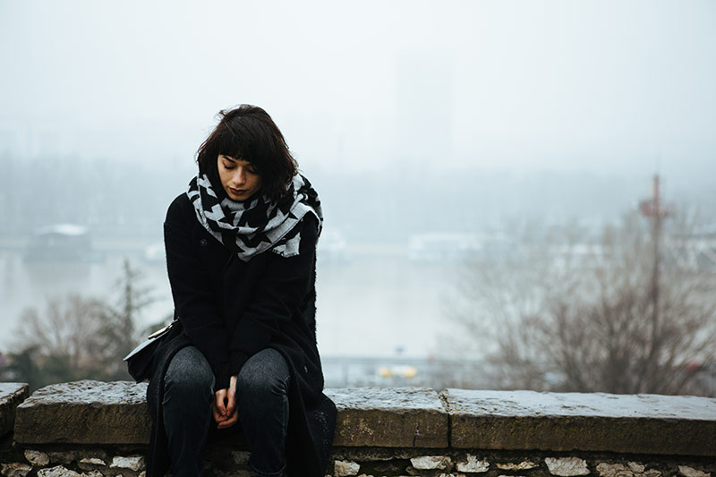 woman sitting along on a bridge in the fog. wanting to be along is among the signs of mental illness.