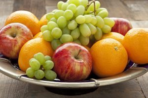 a bowl of apples, oranges and grapes