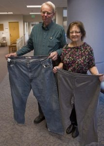 Diane and Dan Hopmann show off pants they used to wear. Dan lost 114 pounds and Diane lost 104.