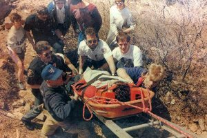 In this newspaper photo from the Coloradoan, PVH EMS paramedic Steve Main (center responder with white uniform) helps firefighters and other rescuers lift a 26-year-old hiker out of a rocky area of Horsetooth Reservoir in March 1993. The hiker was treated at PVH for facial-bone fractures, head injury and cuts and scrapes, and was later released.
